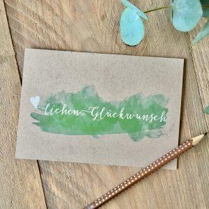 Grußkarte zum Geburtstag mit weißem Lettering und grüner Aquarell-Wolke auf Kraftpapier